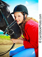 equestrian - pretty young woman with a black horse