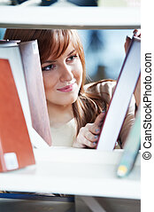 young student girl at book shelf in library