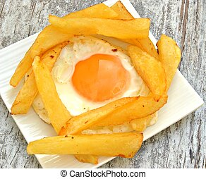 Fried egg with several chips served on a plate on wooden...