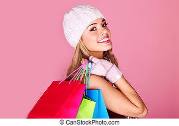 Happy Young Shopper. Pretty smiling girl in winter cap with...