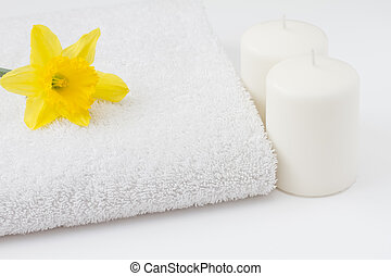 White towel with candles and daffodil spa concept