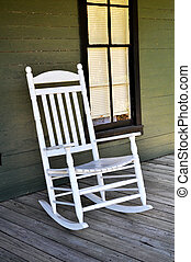 White Rocking Chair - A white wooden rocking chair is...