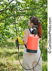 Woman spraying tree plant in orchard