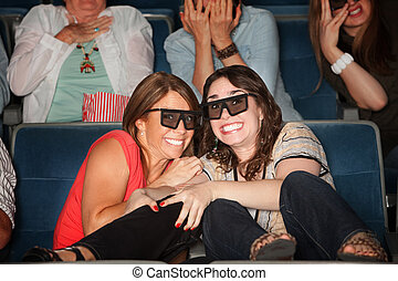 Scared Friends in Theater Seats - Two frightened women with...