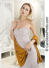 elegant pretty young woman with a long scarf and a lighter dress, she looks in to the lens, her right hand is on the chest and she takes the end of the scarf with left hand