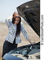 woman looking under car hood - middle age woman looking...