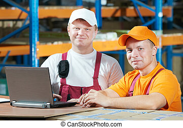 manual workers in warehouse - two young handsome workers man...