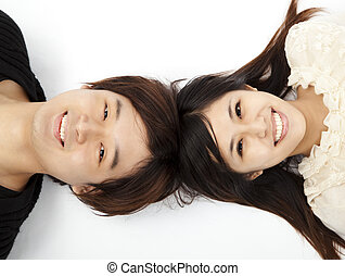 young lovely couple lying on the white floor and looking the camera
