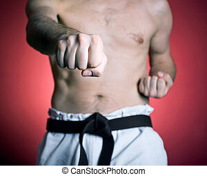 Practice karate punch - Young man practicing karate over red...