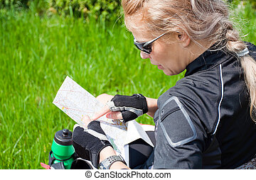 Woman on bicycle trip checking a map