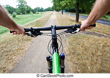 Riding a bike - Bicycle rider riding on dirt bike path,...