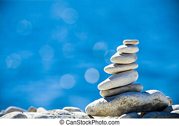 Stones stack over blue sea - Close-up of white pebbles stack...