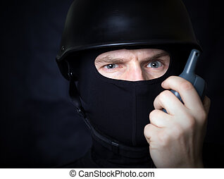 Man talking by walkie talkie radio - Man in helmet and mask...