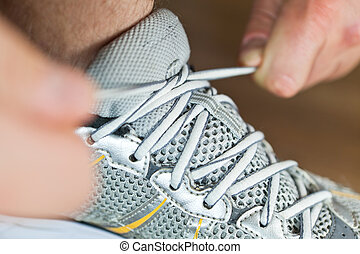 Sport shoe tying - Man tying sports shoe at gym before...