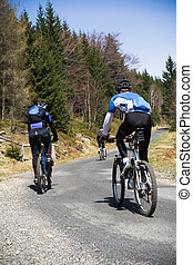 Mountain bikers going uphill - Mountain bikers riding on...