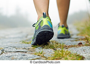Walking exercise - Woman walking in mountains in sport shoes