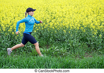 Woman running outdoors on spring - Athletic woman running on...