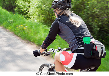 Woman riding a bike, motion blur - Young woman riding...