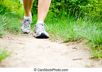 Woman walking on trail in forest
