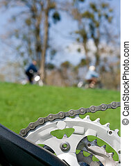 Bicycle chain over blurred cyclist - Chain and bicycle...