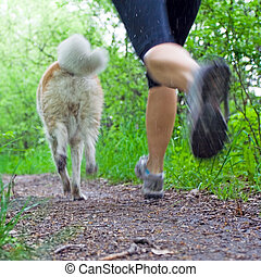 Woman running with dog in forest