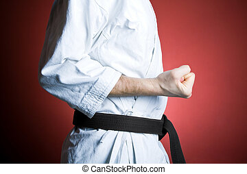 Karate punch - Young man practicing karate over red...