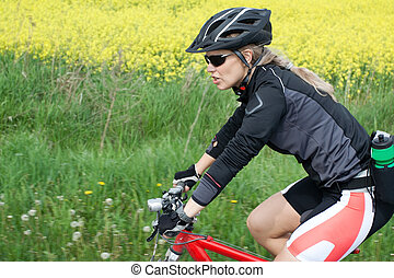 Riding on mountain bike in summer - Young woman ride on...