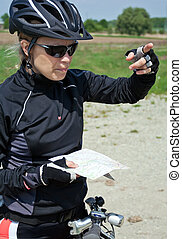 Woman on bicycle checking a map