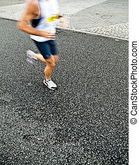 Man running in city marathon, motion blur