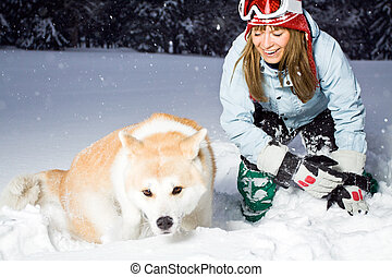 Woman and winter fun with a dog - Woman snowboarder having...