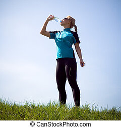 Drinking water after running outdoors - Woman taking a break...
