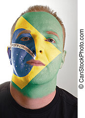 Face of serious patriot man painted in colors of brazil flag