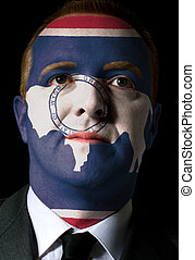 High key portrait of a serious businessman or politician whose face is painted in american state of west wyoming flag