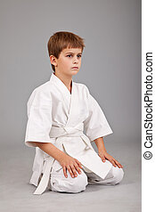 Karate boy in white kimono is sitting isolated on gray...