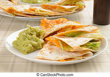 Cheese quesadilla with guacamole - A plate of cheddar cheese...