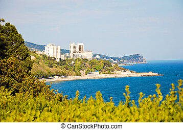seaside resort with blue water, sky and trees