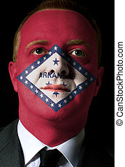 High key portrait of a serious businessman or politician whose face is painted in american state of west arkansas flag