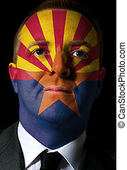 High key portrait of a serious businessman or politician whose face is painted in american state of west arizona flag
