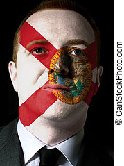 High key portrait of a serious businessman or politician whose face is painted in american state of west florida flag