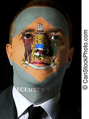 High key portrait of a serious businessman or politician whose face is painted in american state of west delaware flag