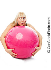 young blond woman embracing a fitness ball isolated against...