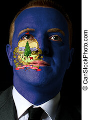 High key portrait of a serious businessman or politician whose face is painted in american state of vermont flag