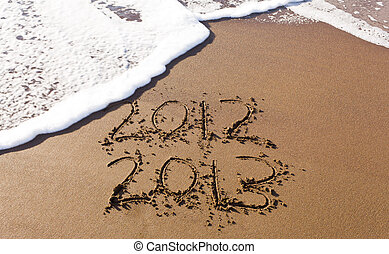 2012 and 2013 written in sand with waves