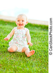 Happy baby playing on grass