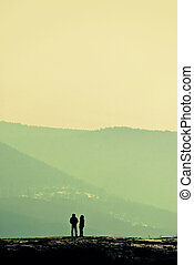 solitude, silhouettes of a man and a woman standing on the...