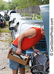 Under the Hood at the Junkyard - A man looks for car parts...