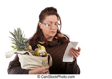 Grocery Shopper Counting Costs - Middle aged woman carefully...