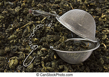 Tea strainer - strainer against the background spilled green...
