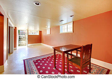 Large basement room with desk and orange walls - Large...