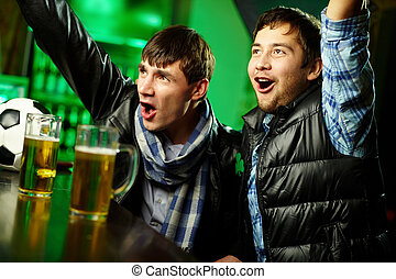 Sport pub - Two guys watching sports at bar and rejoicing